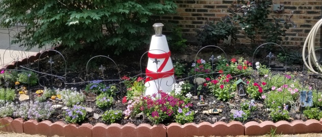 A fairy garden with a pot sculpture of a lighthouse